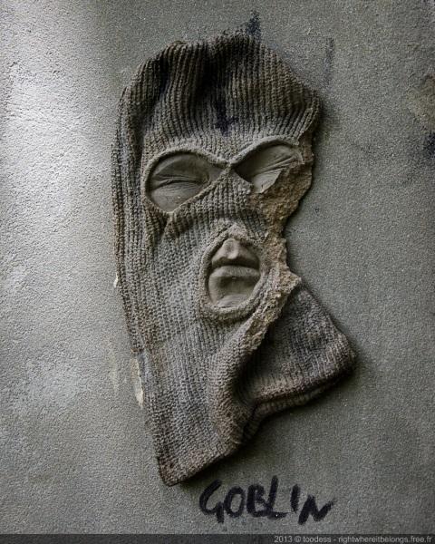 Sculpture visage cagoulé sur mur à Sydney