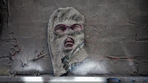 Sculpture visage cagoulé sur mur à Melbourne